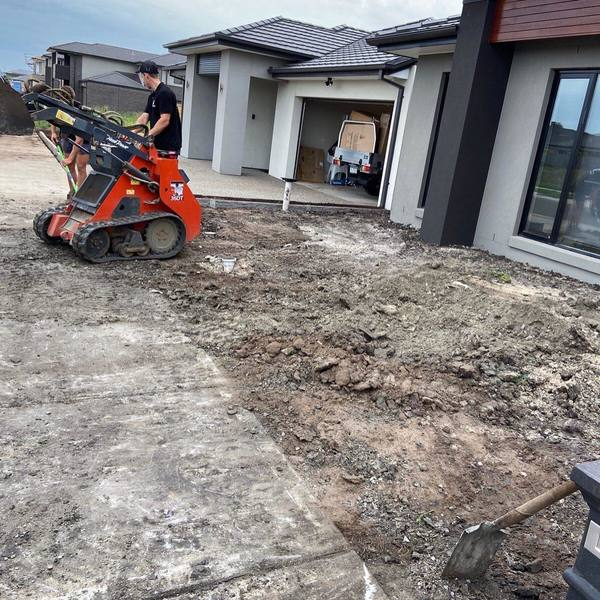 A man driving an excavator to perform a landscaping task.