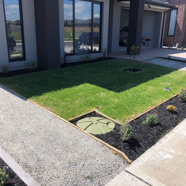 A front lawn with natural turfing and a small garden bed with a few plants in Melbourne.