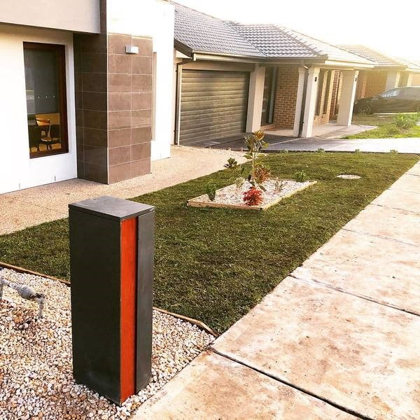 A red and black letterbox on a front lawn with white stones and green, natural turf (lawn).