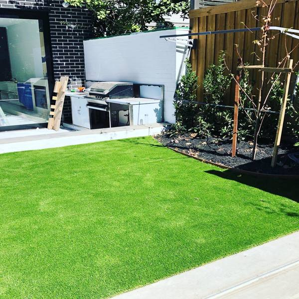 A landscape of a synthetic, green lawn with a garden bed.