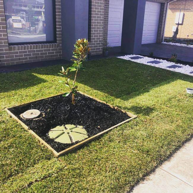 A front lawn with some natural turfing laid down with a garden feature piece at a Melbourne home.