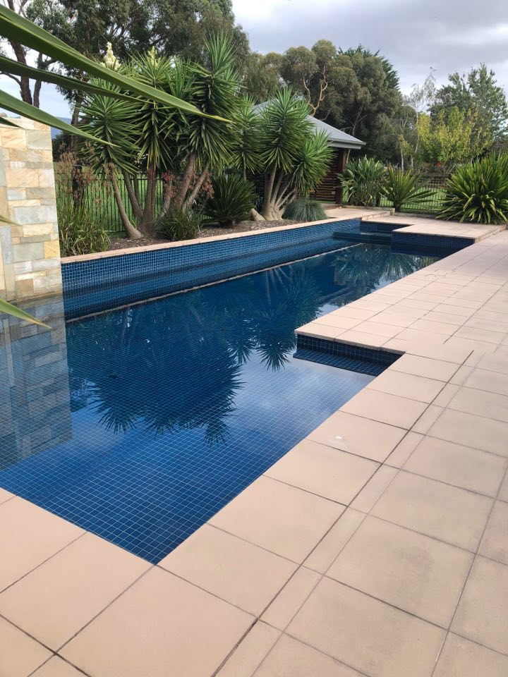An outdoor, blue pool surrounded by sandstone pavers.