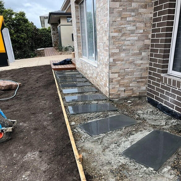Bluestone pavers in an unfinished front yard.