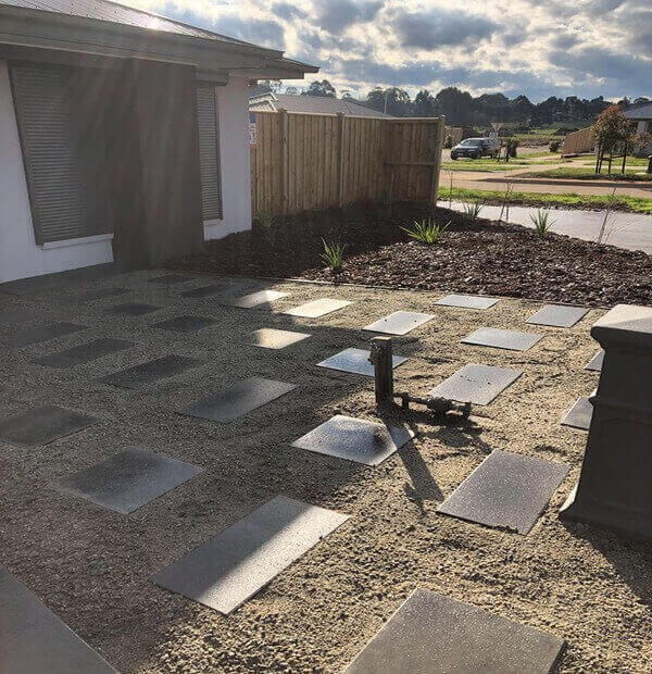 Black concrete pavers in a front yard.