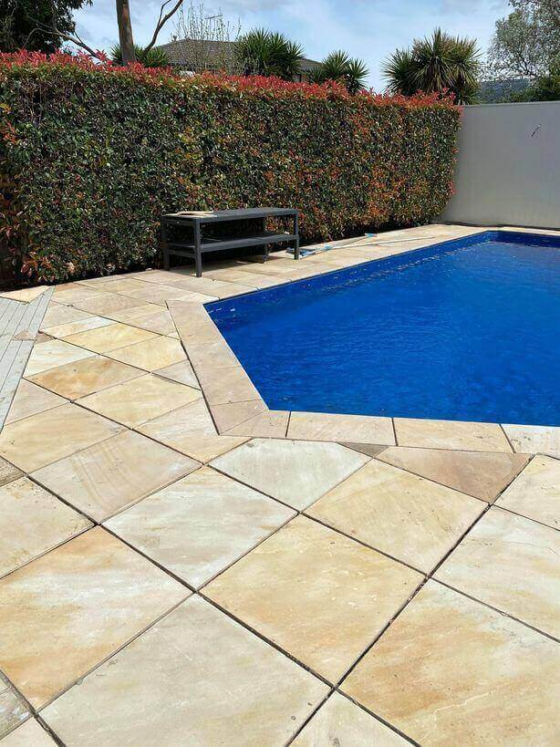Sandstone pavers around a blue pool.