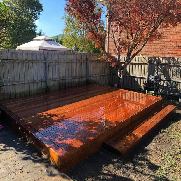 A varnished, timber decking in a backyard next to a tree.