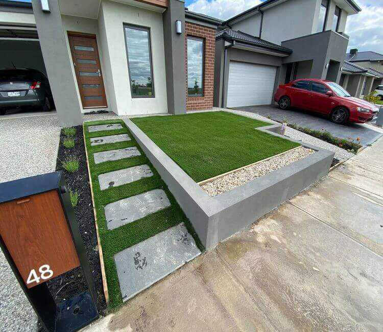 A rendered block retaining wall with artificial grass and bluestone pavers at a Melbourne property.