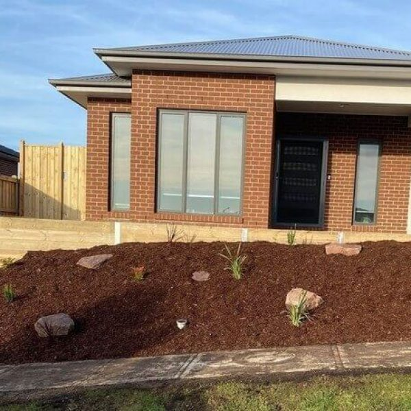 A timber retaining wall with steel sleepers and a tanbark garden with a letterbox.