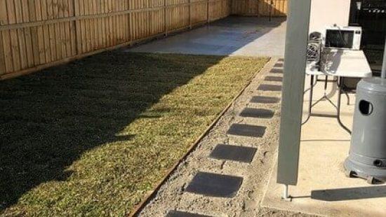 Black concrete pavers in a domestic backyard.