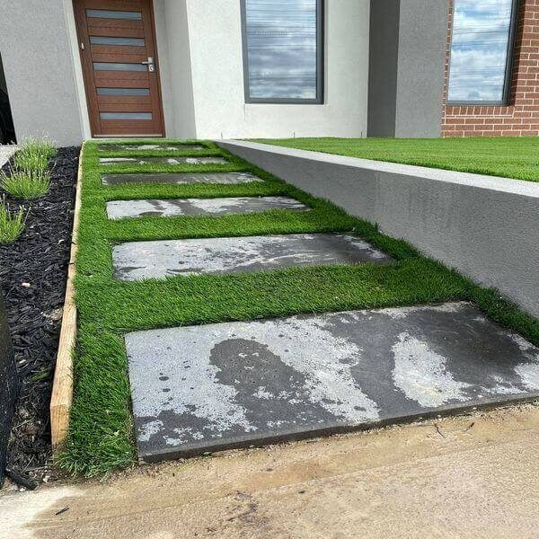 Bluestone pavers on artificial turf in a south eastern Melbourne front yard.