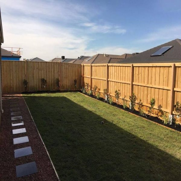 A backyard with a wooden fence, concrete pavers, natural turfing and a garden bed.