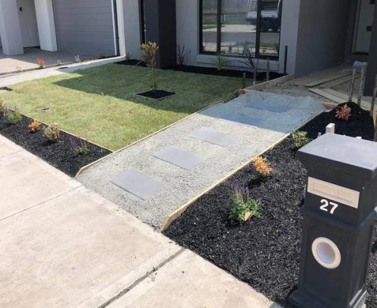Natural front lawn turf, with a grey pavement and black letterbox.