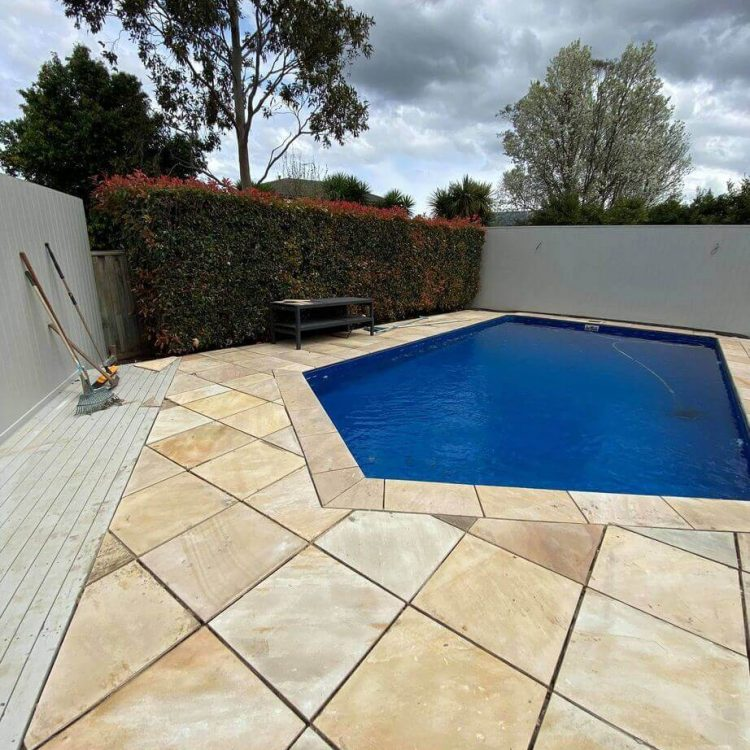 A wide angle shot of sandstone pavers next to an ocean blue pool.