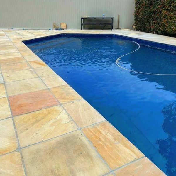 Sandstone pavers next to a blue pool with a water hose in the pool.