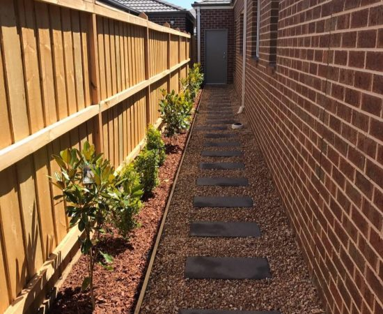 A set of paved steps next to a landscaped garden bed.